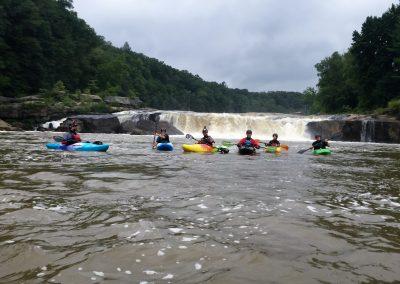 group of kayakers below ohiopyle falls