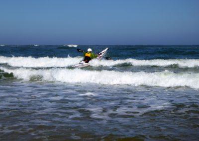 kayaker breaking out through surf