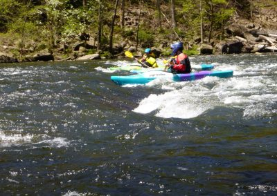 2 kayakers surfing a wave on the pigeon river