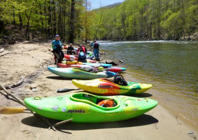 line of kayaks taking alunch break on the pigeon river