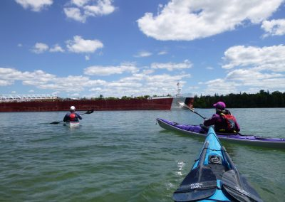3 kayakers and freighter