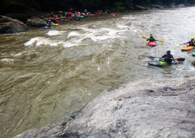 kayakers waiting to surf the wave at swimmers rapid