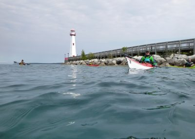 wawatam lighthouse with 3 kayakers